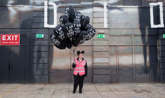 "One of the park's purposefully morose employees sells ""I Am An Imbecile"" balloons. (Photo: Alicia Canter/""The Guardian"")"
