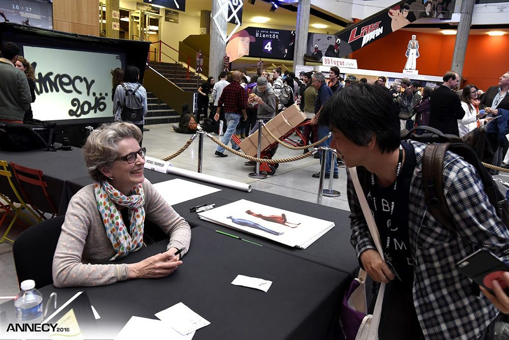 Michèle Lemieux, NFB director, pinscreen animator, and artist of this year's Annecy poster, talks with a fan at a poster signing session. (Photo : F. Blin/CITIA)
