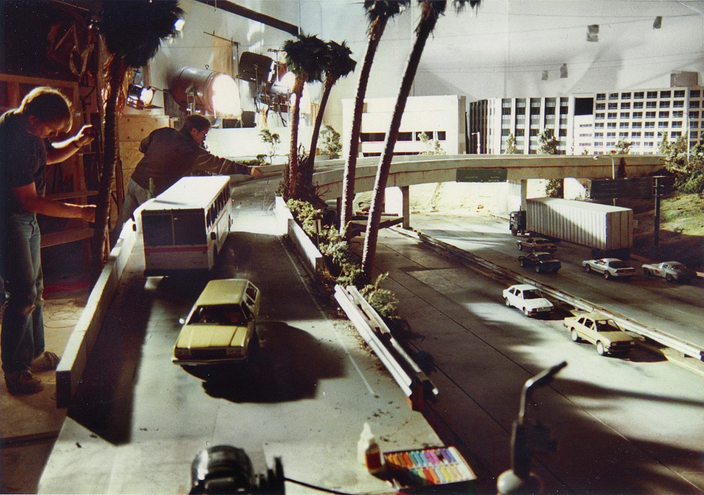 Setting up the freeway miniature. Robert Skotak is leaning over the freeway at rear.