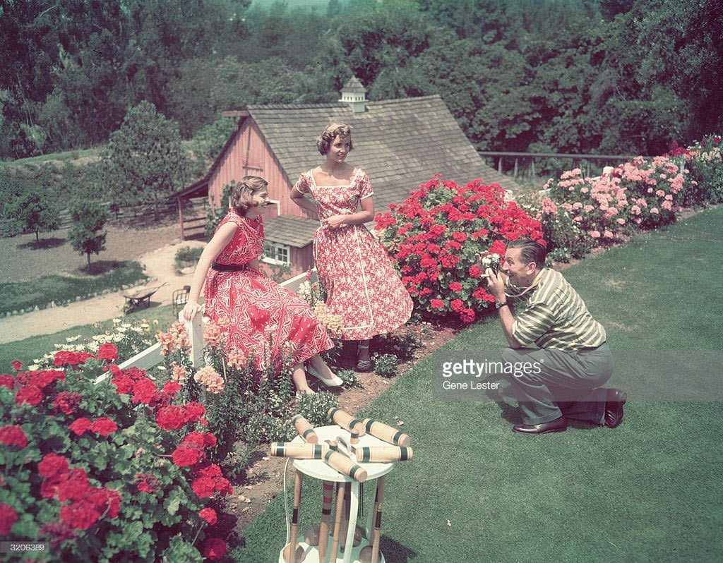 Walt Disney photographing his daughters Diane and Sharon at home.