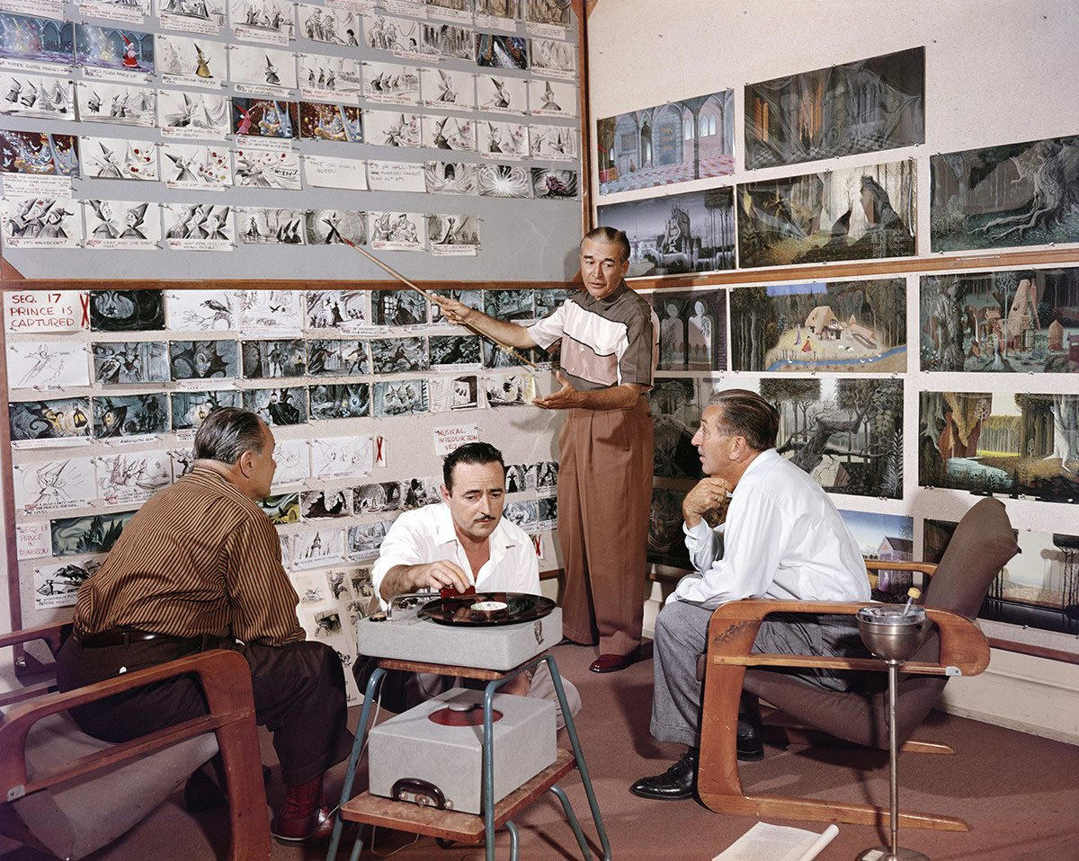 "Walt Disney reviewing ""Sleeping Beauty"" boards with director Clyde Geronimi (left), storyman Joe Rinaldi (middle), and another unidentified person (possibly Ed Penner shortly before his death)."