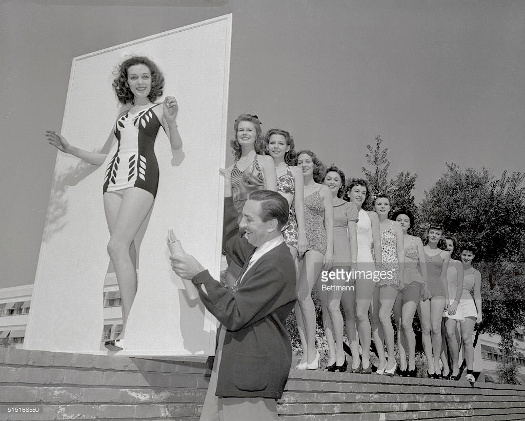 "The original newspaper caption for this photo reads: ""Helen Bradbury steps through a cut-out model as Walt Disney checks the list."""