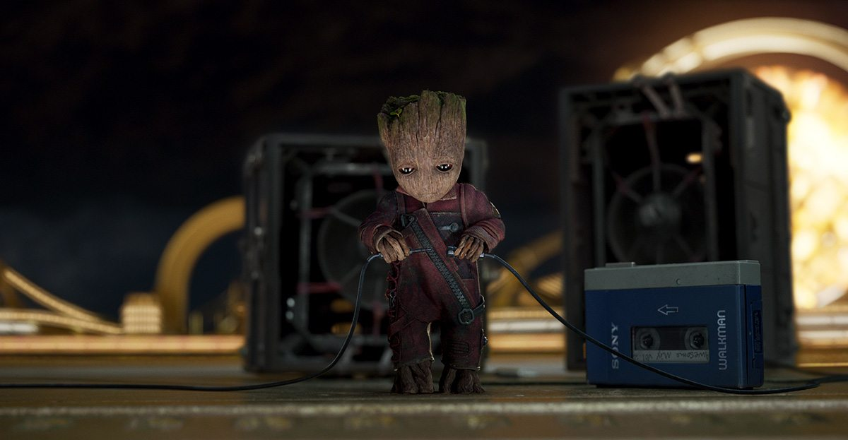 Baby Groot (voiced by Vin Diesel) prepares to rock out while his friends fight a giant Abelisk.