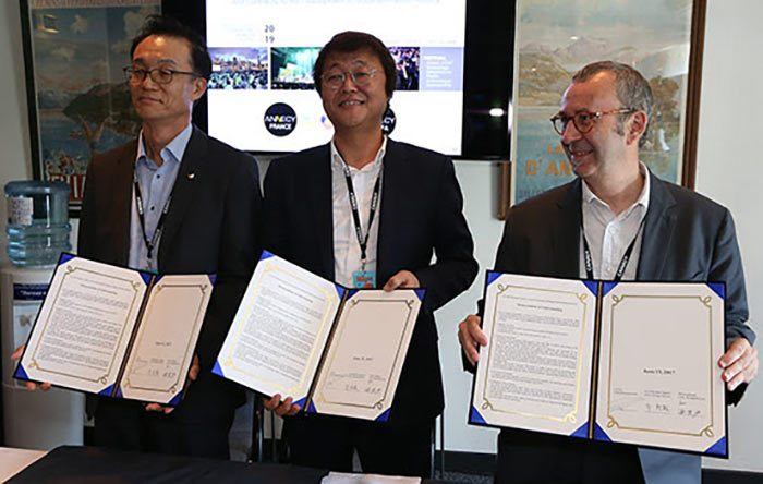 Harry (Sang Chul) Yoon of SK Broadband, Hyungchul Joo (SBA - Seoul Animation Center), and Patrick Eveno (CITIA) signing the Annecy Asia partnership agreement last Tuesday in Annecy. Photo: G. Piel/CITIA.