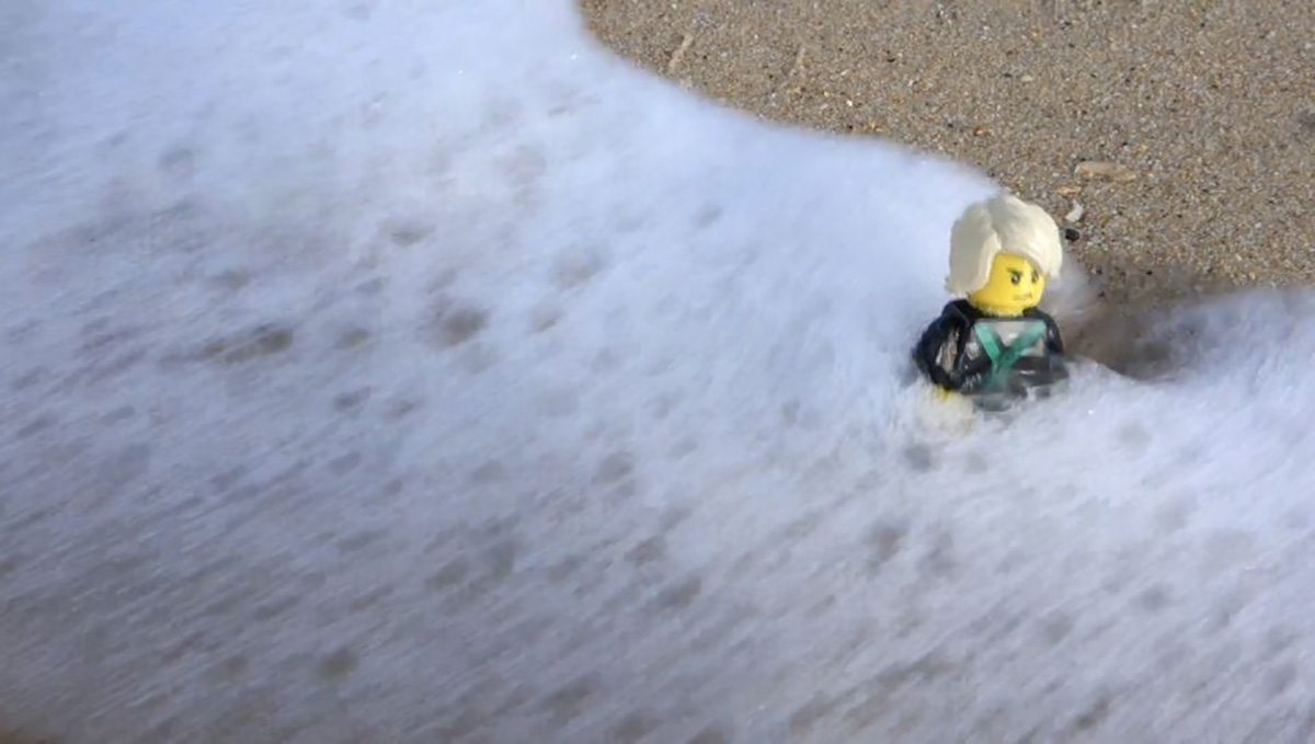 Closer view of the concept minifig amongst sand and foam at Bondi Beach.