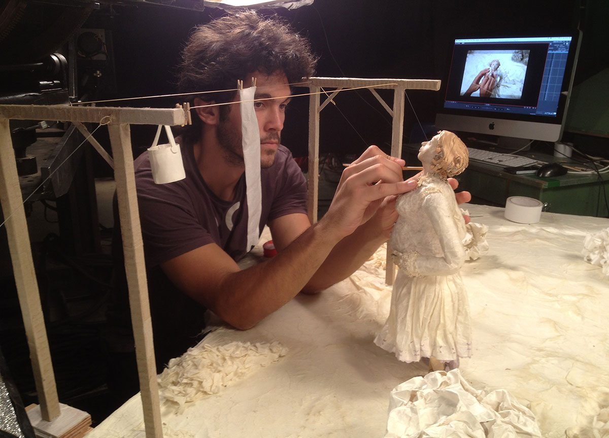 "Animator working with a papier-mâché puppet from ""Women's Letters."""