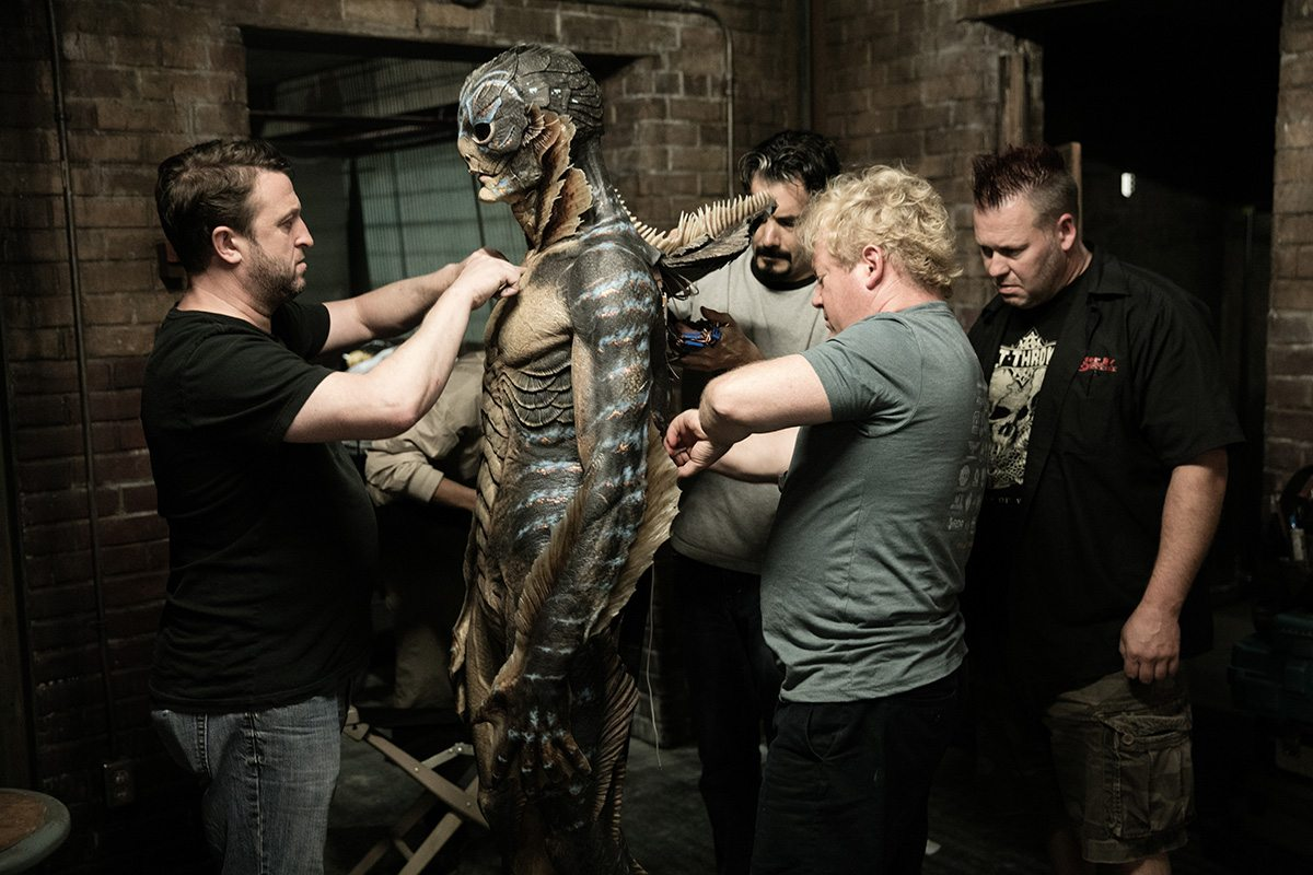 """Shane Mahan (second from right) and other Legacy Effects crew members work on the prosthetics worn by Doug Jones on the set of """"The Shape of Water."""""""