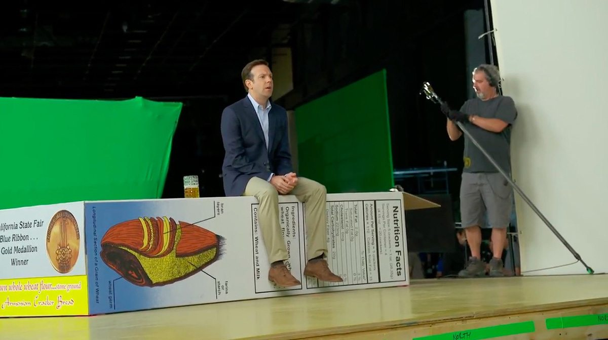 A screenshot of Jason Sudeikis from b-roll footage shows him performing against greenscreen on an oversized set.