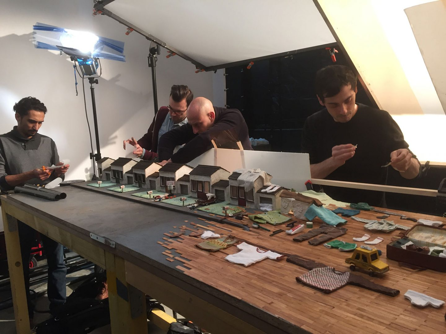 One of the largest sets - the pan of suburb - being lit. The team is using gels and gaffer tape to control small lighting details. From left: Walid Païenda (production assistant). Simon Gesrel (cinematographer), Jean-Louis Padis (co-producer), and Max Porter (co-director).