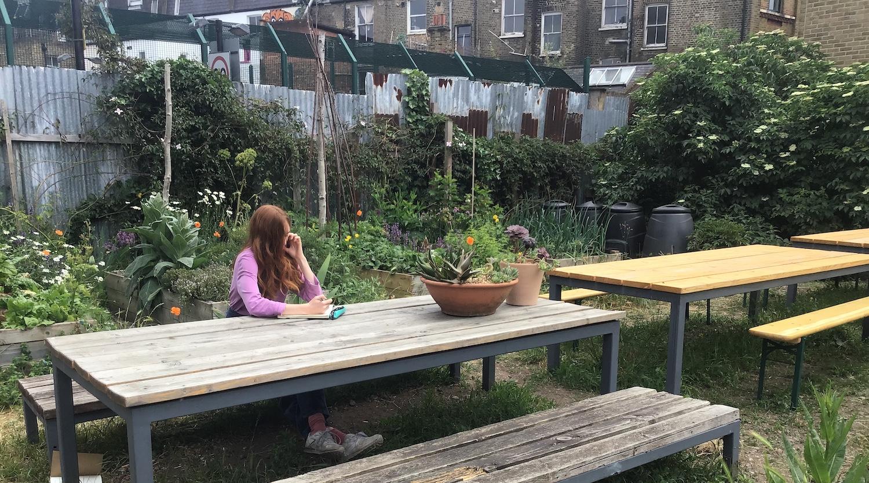 Gate sketching in her studio's vegetable garden.