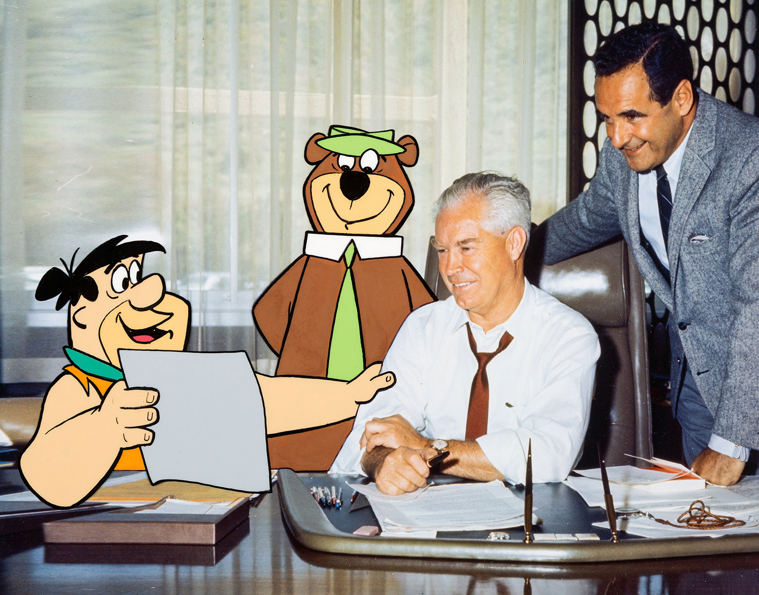 Bill Hanna (left) and Joe Barbera, pose with two of their studio's stars, Fred Flintstone and Yogi Bear.